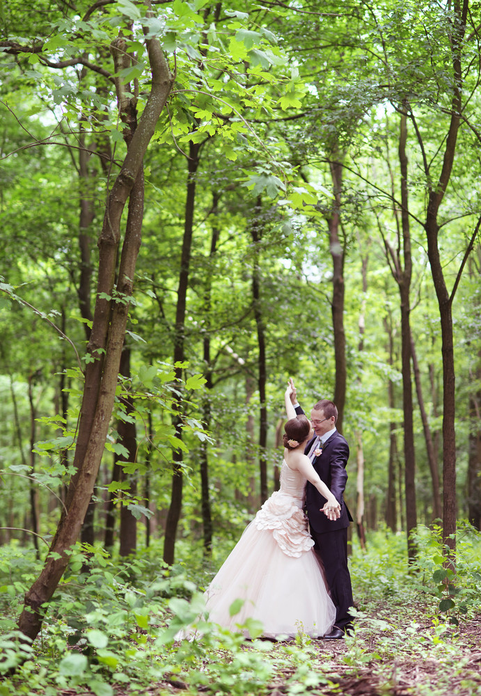 Wedding couple - bride and groom - taking a walk in the park.