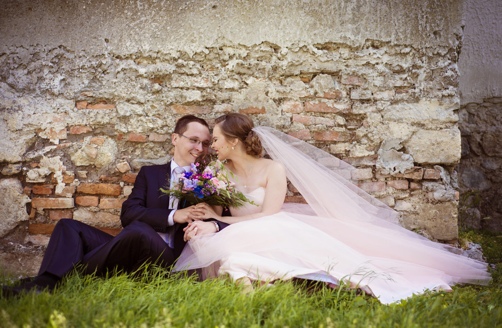 Wedding couple of bride and groom sitting by old stone wall.