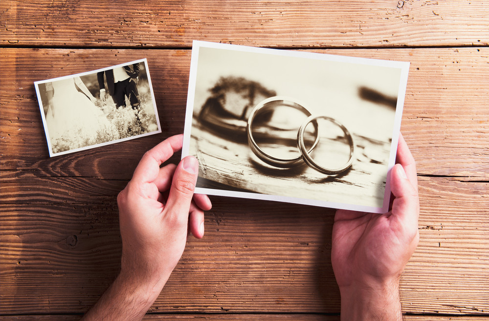Wedding photos laid on a table. Studio shot on wooden background.