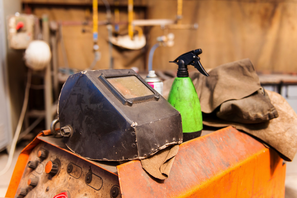 Welding shield laid on a welding machine and other equipment in small factory hall