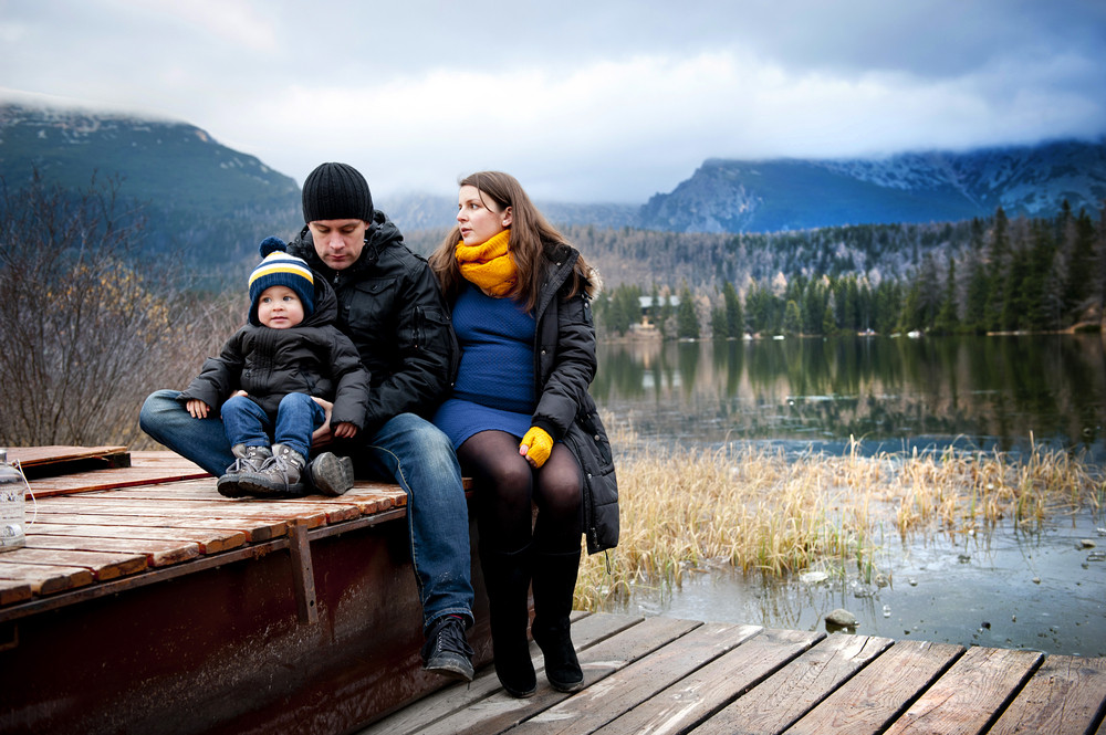 Winter portrait of pregnant mother and father with little boy sitting on pier by the lake with mountains in background