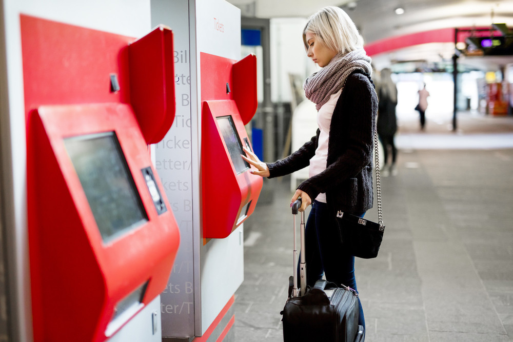 Woman Buying Train Ticket Using Vending Machine At Station