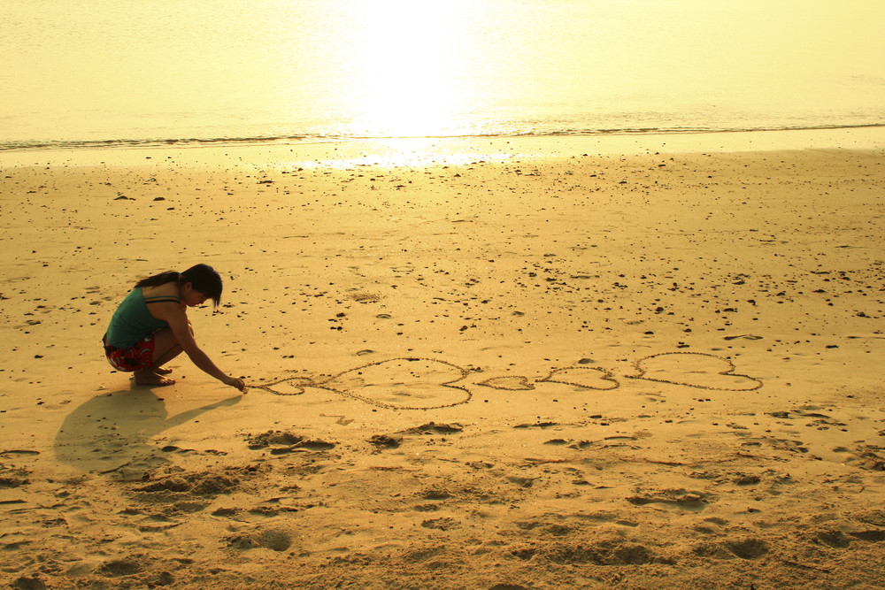 Woman drawing a heart symbol in sand.