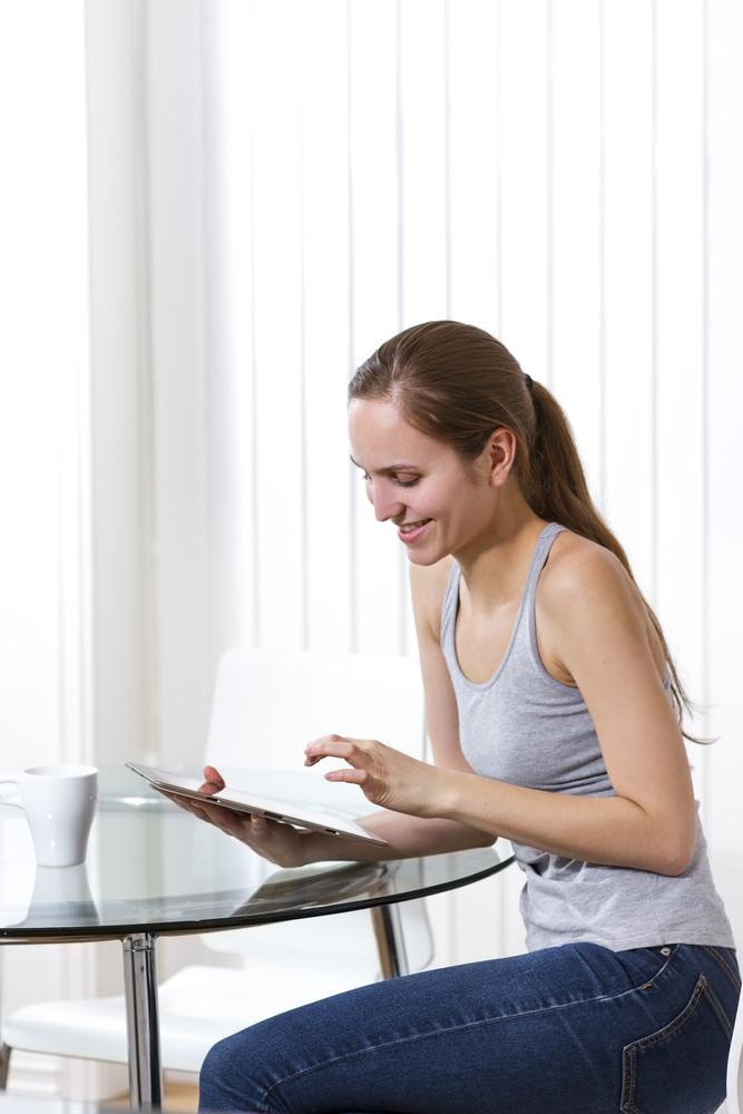 Woman drinking coffee and using pad in a white room. Copy Space