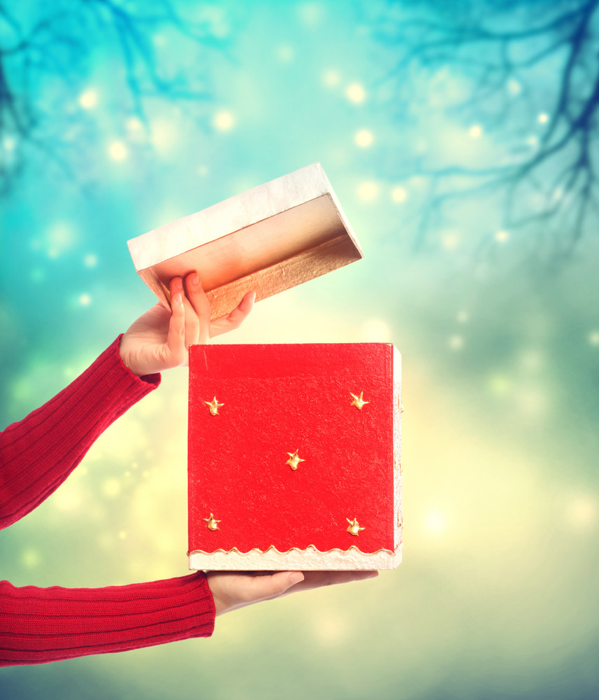 Woman holding a red gift box on bright holiday lights background