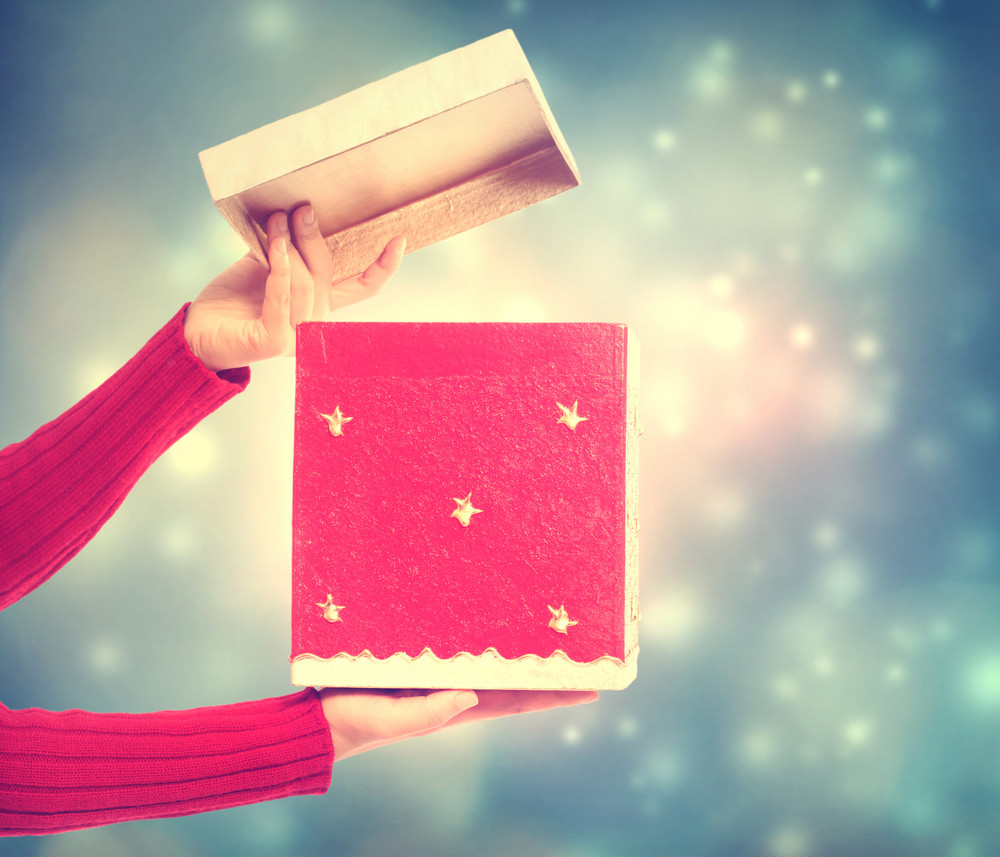 Woman holding a red gift box on holiday lights background