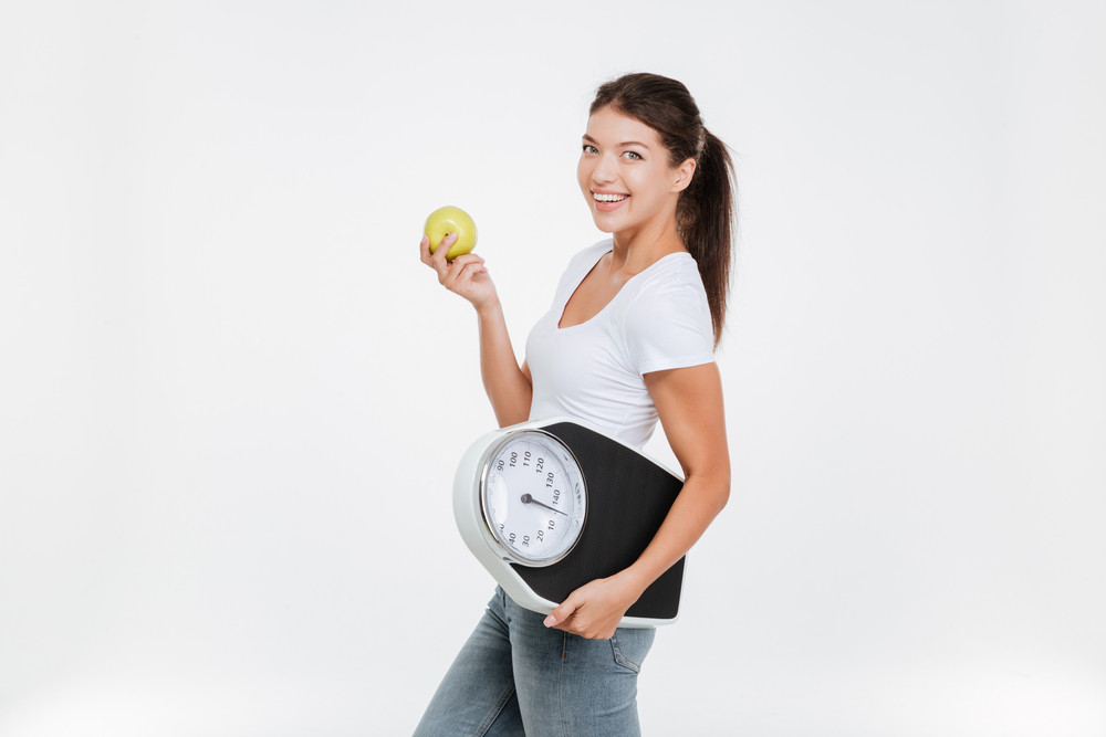 Woman holding scale and apple for healthy lifestyle and nutrition. Isolated over white background. Looking at camera.