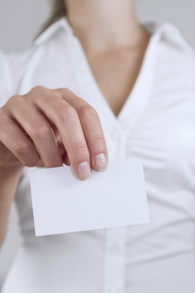 Woman holds out business card. Place your business card or corpate logo on the card.