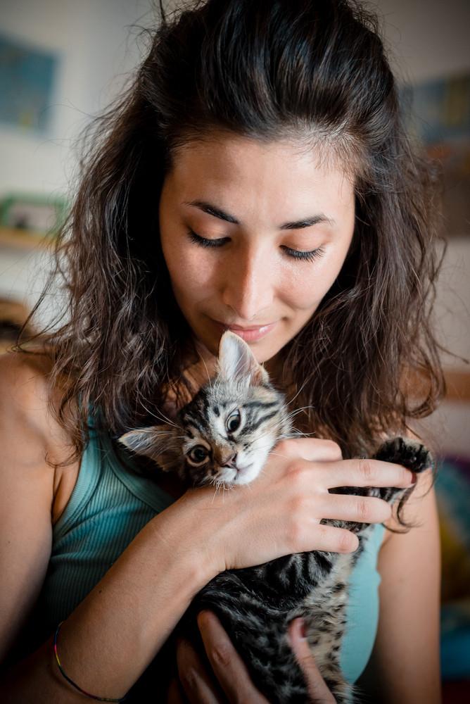 woman hugging cat at home