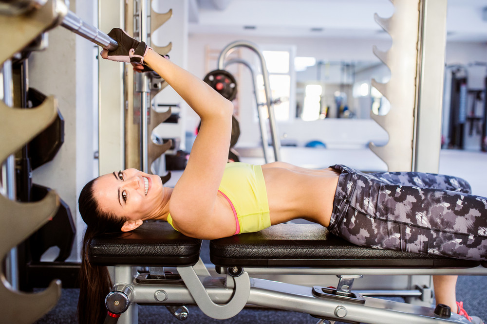 Woman in a gym working out with weights, bench pressing