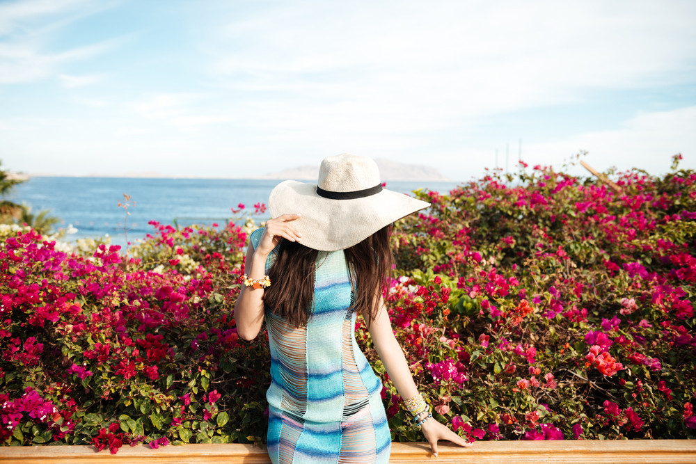 Woman in beachwear and hat with flowers on background