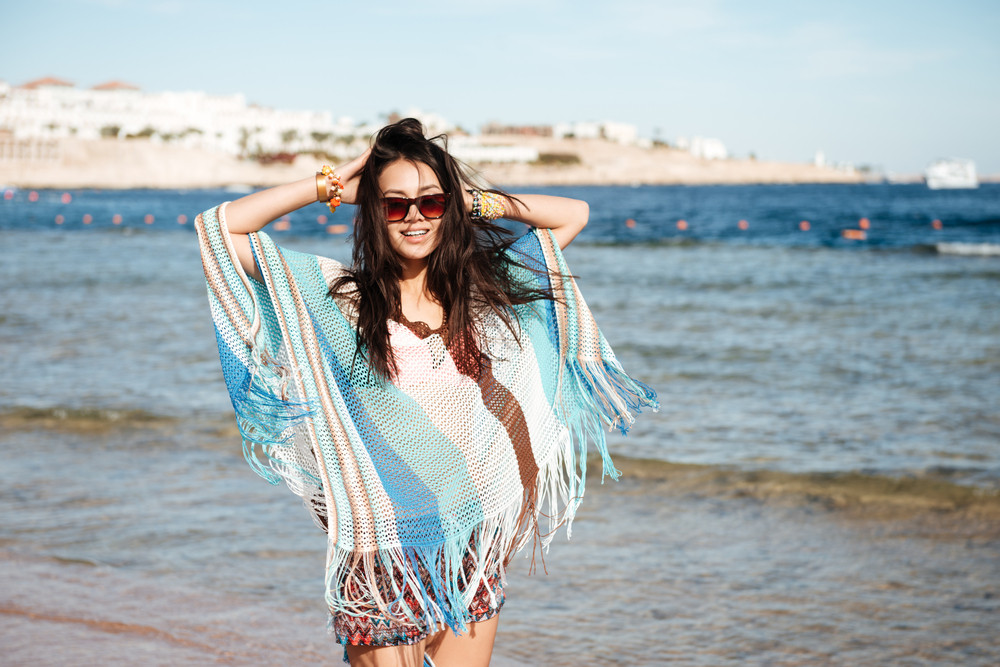Woman in beachwear and sunglases which standing on the beach near the sea