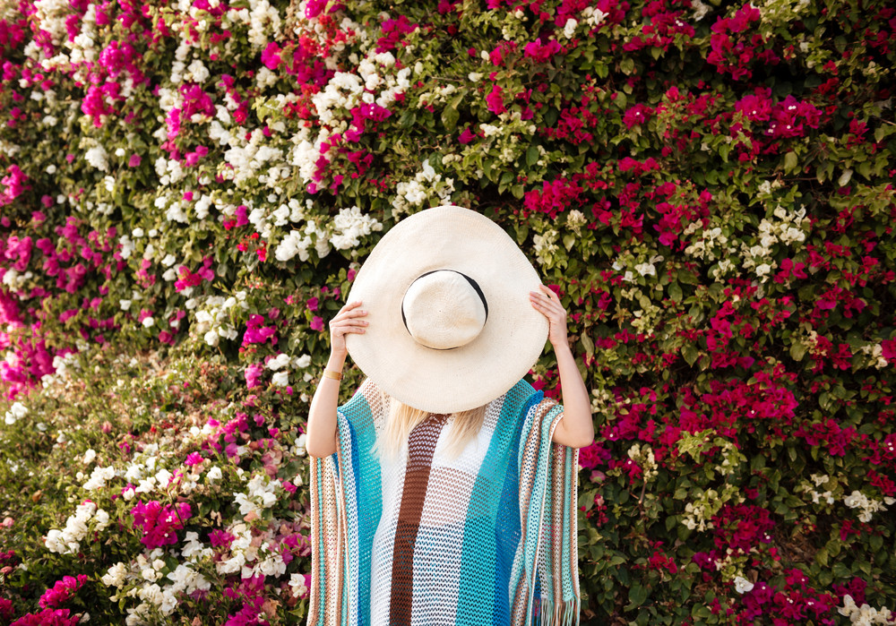 Woman in beachwear which hiding behind the hat with flower bush on background