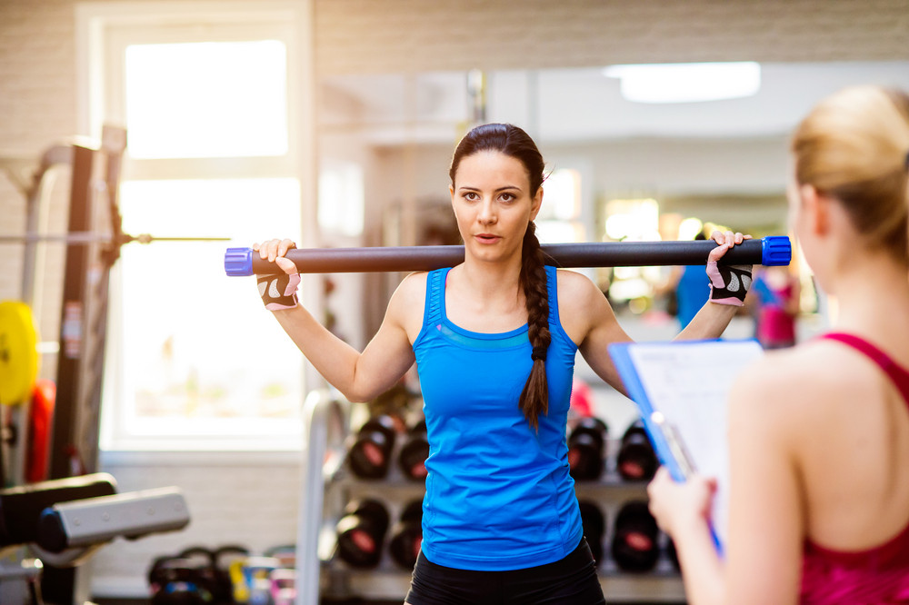 Woman in blue singlet exercising with bar in a gym  with her personal trainer writing into exercise plan on clipboard