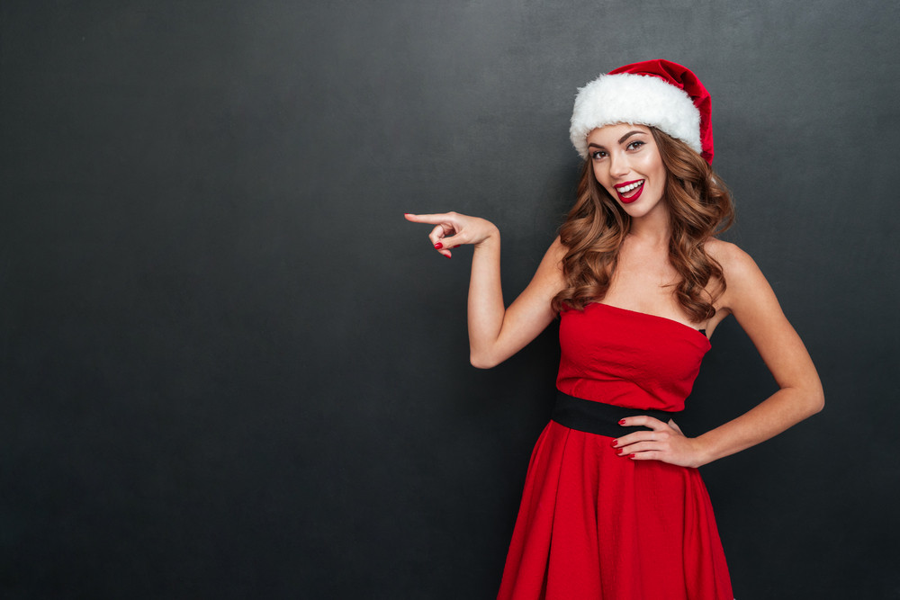 Woman in Christmas dress shows the finger. One hand on the belt. Black background