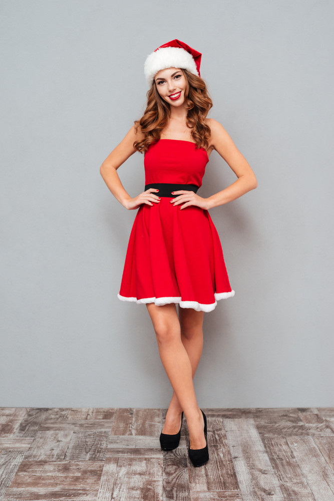 Woman in dress and Santa's hat stay on the floor over gray background
