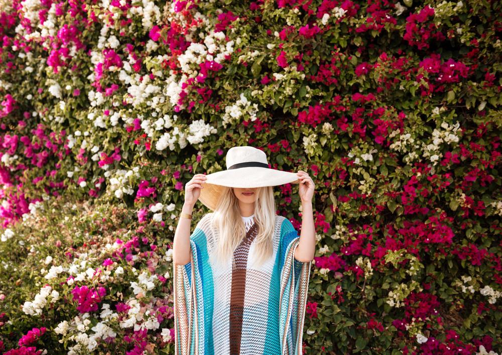 Woman in hat and beachwear which posing near the flower bush