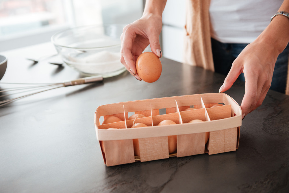 Woman in kitchen with eggs. cropped image