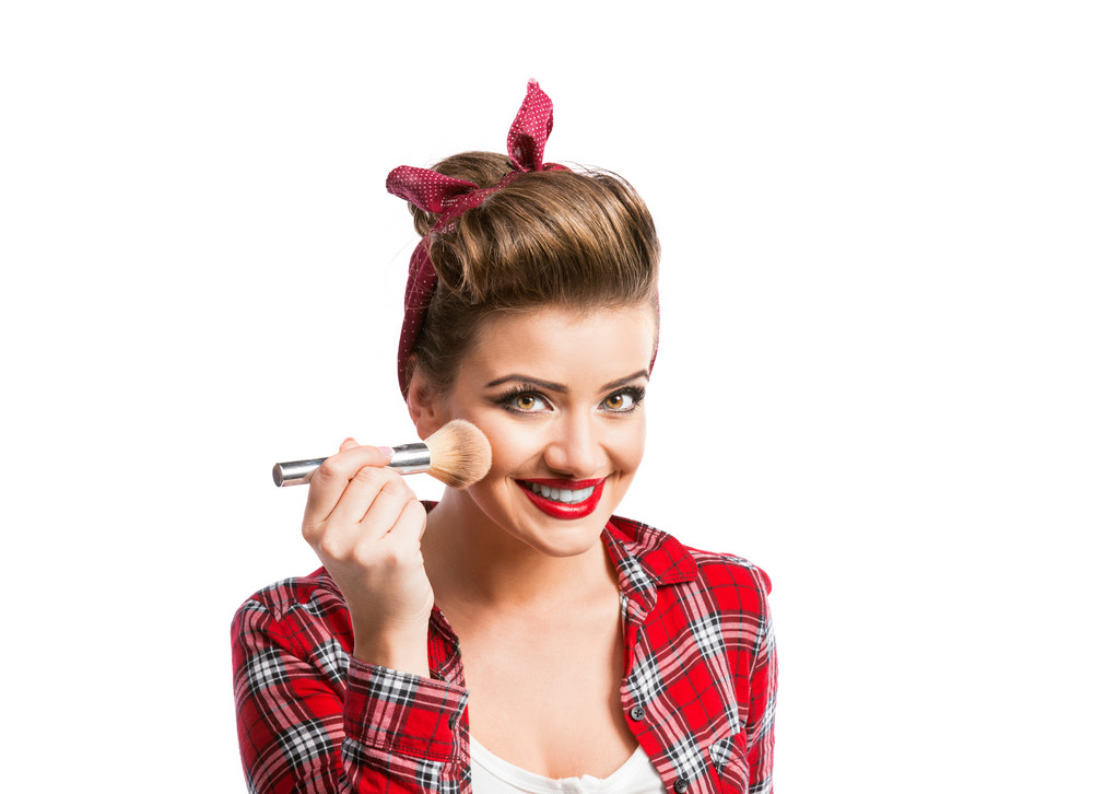 Woman in red checked shirt with pin-up hairstyle applying make-up with a brush. Studio shot on white background