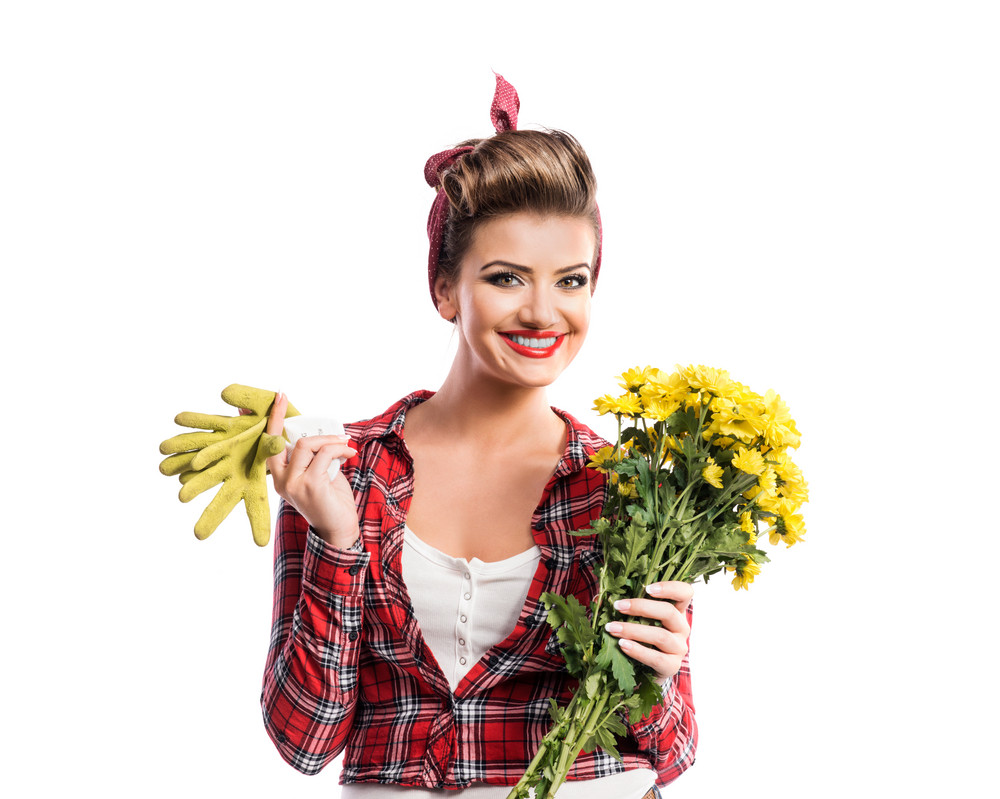 Woman in red checked shirt with pin-up make-up and hairstyle holding yellow daisies. Studio shot on white background