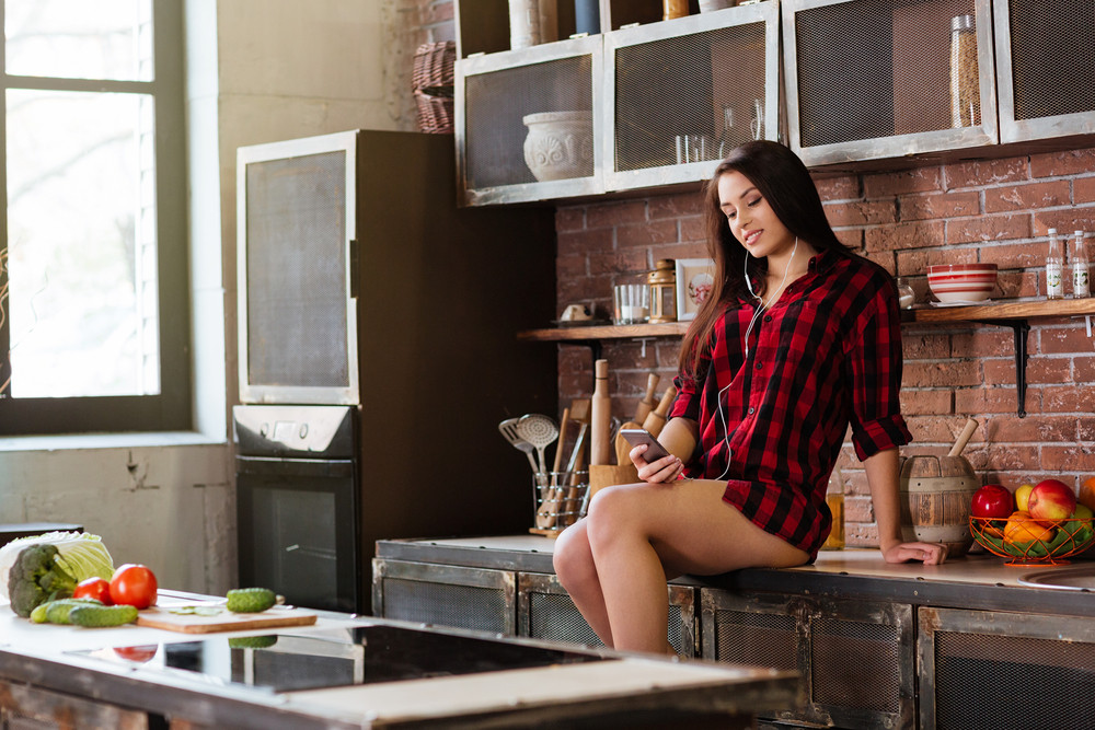 Woman in red shirt with naked legs sitting on the table and listening music on phone in kitchen. Side view