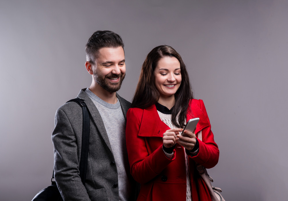 Woman in red winter coat and a hipster man in gray jacket with smartphone. Studio shot on gray background.