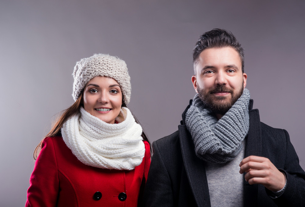 Woman in red winter coat and hipster man with knitted scarf. Studio shot on gray background.
