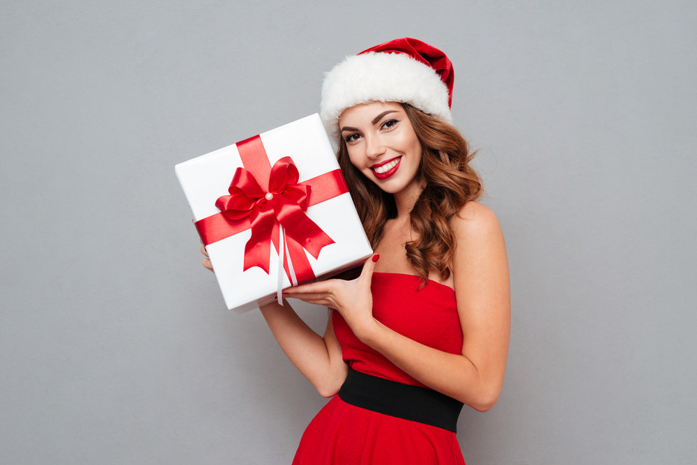 Woman in santa's hat and dress holding a white box with red tape