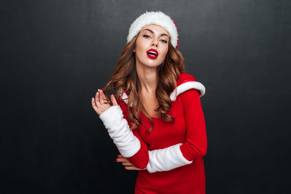 Woman in santas hat and dress looking at the camera over black background