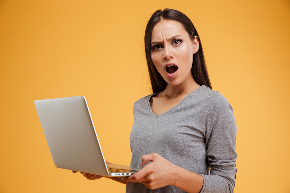 Woman in shock with laptop looking at camera. isolated orange background