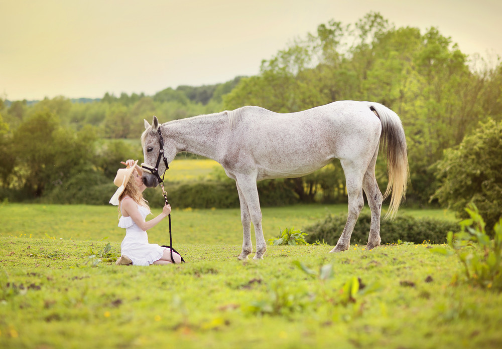 Woman in white dress walking with horse in green countryside