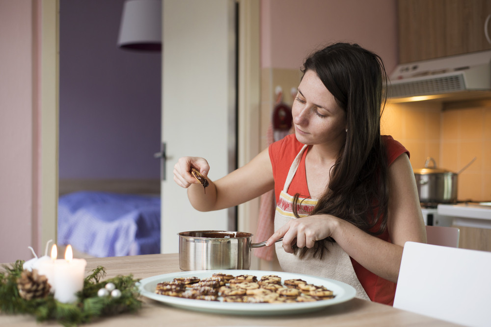 Woman is making christmas cakes in the kitchen