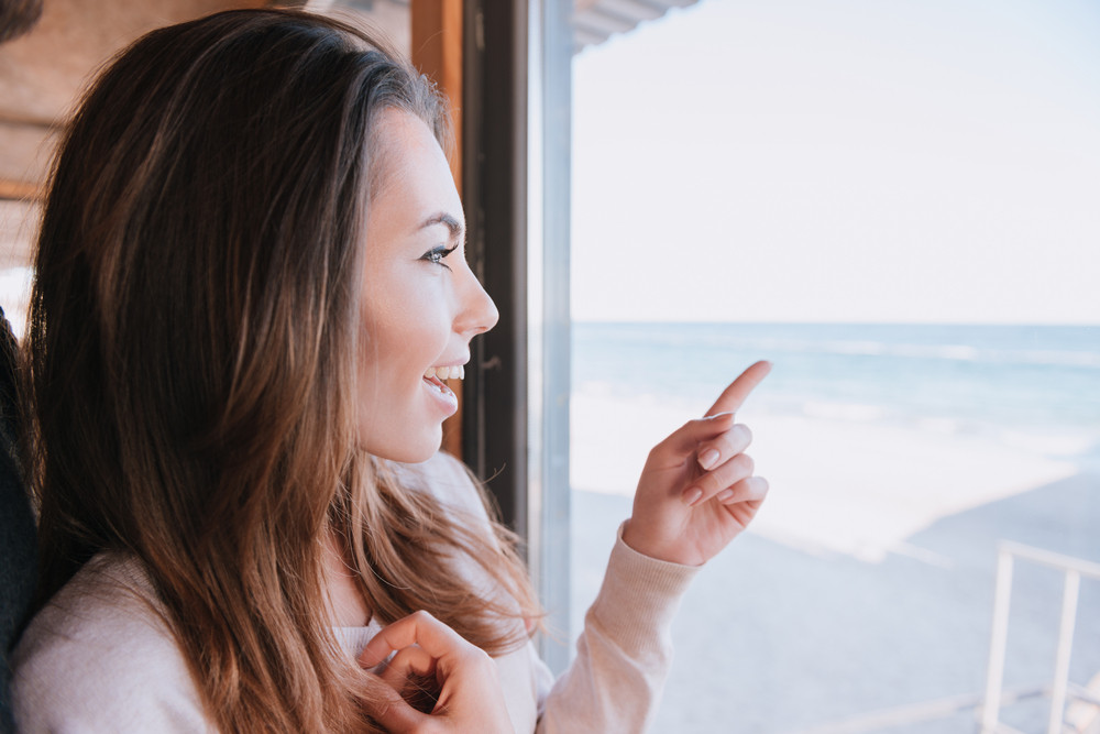 Woman on date near the window in cafe near the sea pointing away. Side view