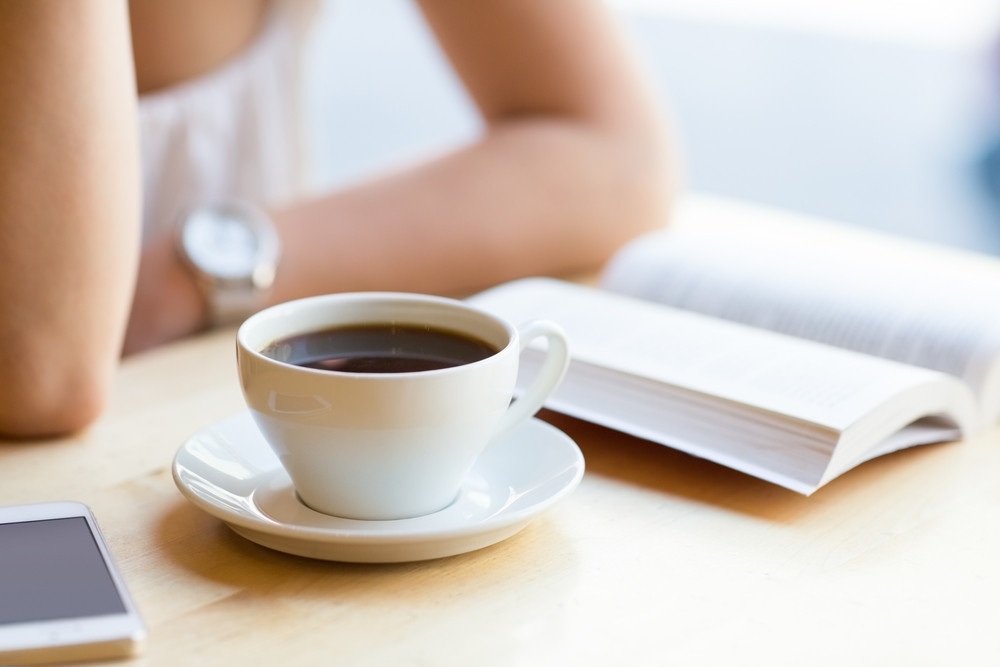 Woman reading book and drinking coffee at cafe