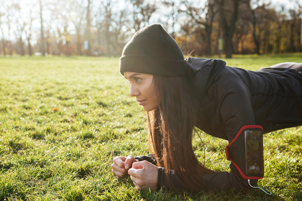 Woman runner in warm clothes and headphones in autumn park make plank