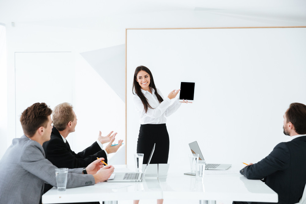 Woman showing blank tablet computer screen and standing near the board on conference with her colleagues which sitting by the table