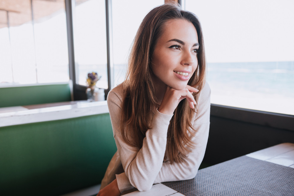 Woman sitting by the table on date in cafe near the sea and looking away
