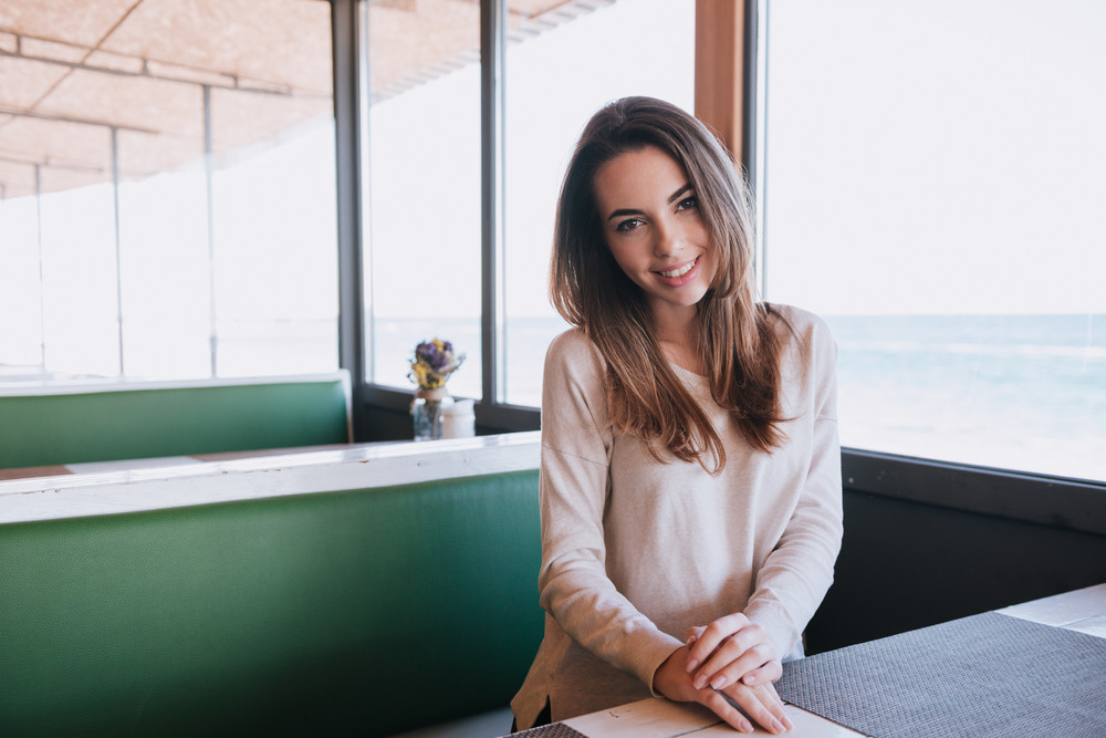 Woman sitting by the table on date in cafe near the sea