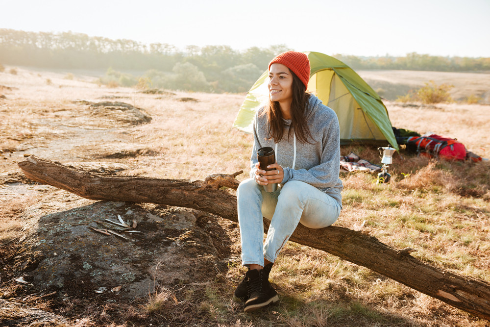 Woman sitting on log near the tent