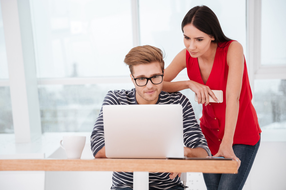 Woman standing near man which sitting by the table with laptop in office. Window on bckground