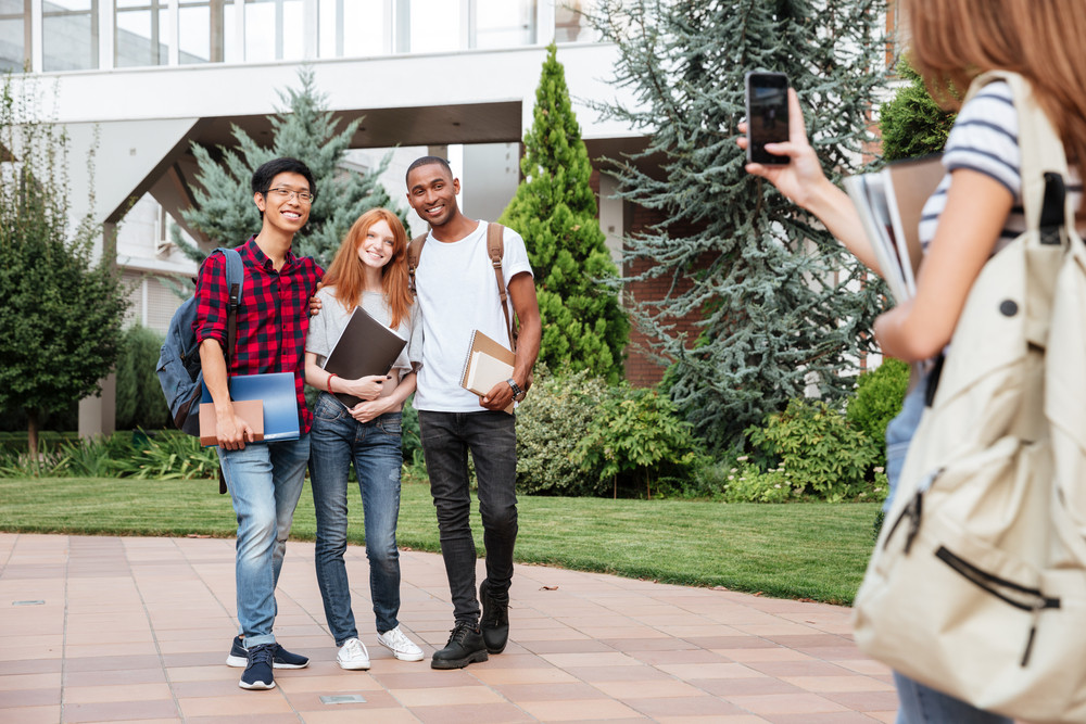 Woman student with backpack taking photos of her smiling friends in campus