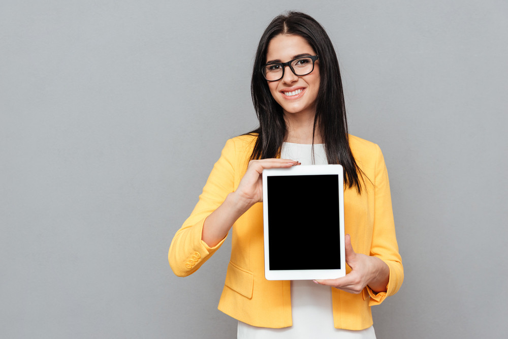 Woman wearing eyeglasses and dressed in yellow jacket showing tablet computer display to camera over grey background. Look at camera.