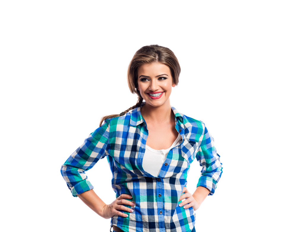 Woman with plait in blue and green checked shirt smiling. Studio shot on white background.