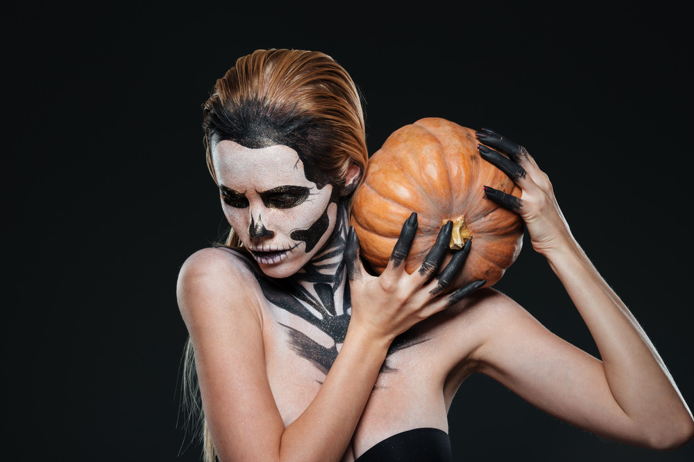 Woman with scared halloween makeup holding pumpkin over black background