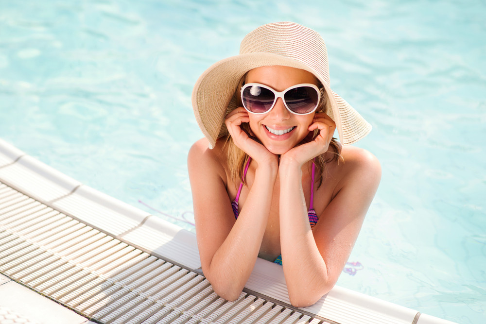 Woman with sunglasses and hat in swimming pool, summer and water.
