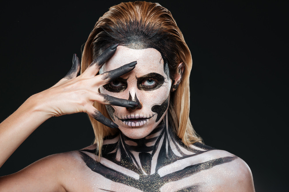 Woman with terrifying halloween makeup over black background