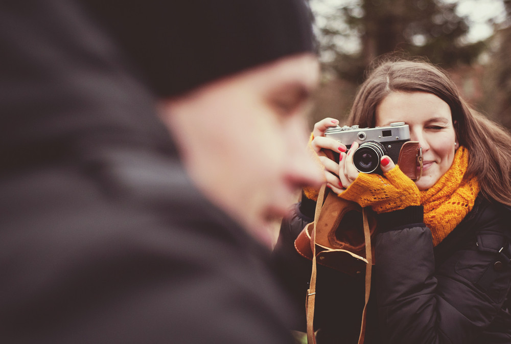 Woman with vintage camera is taking picture of her husband outdoor