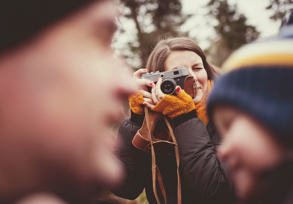 Woman with vintage camera is taking picture of her little son and husband outdoor
