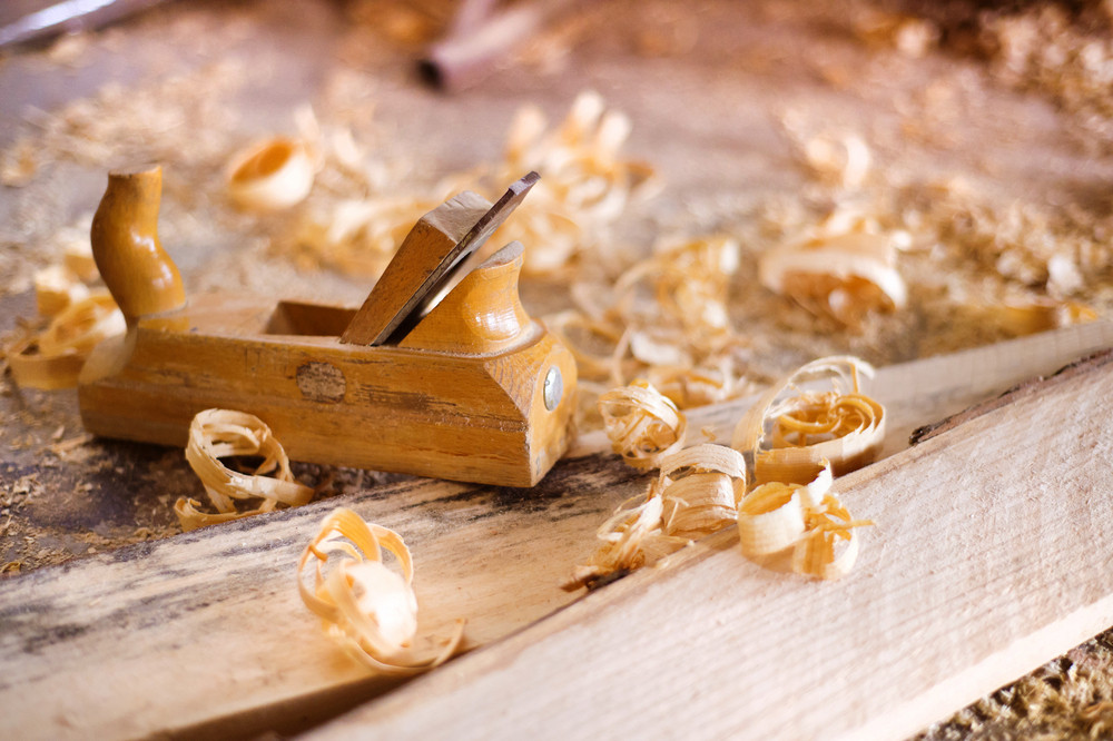Wood planer, wooden planks and shavings at carpenters workshop