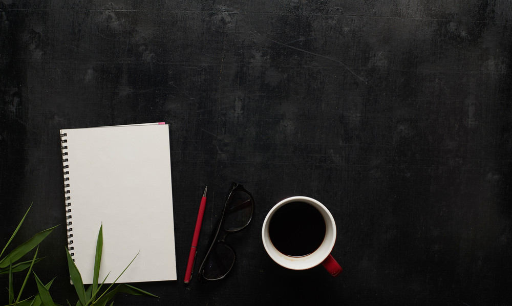 Wooden black office desk table with eyeglasses, notebook and pen with cup of coffee. Blank notebook page for input the text in the middle. Top view